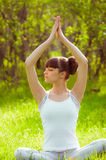 Young girl doing yoga on a green grass Stock Images