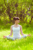 Young girl doing yoga on a green grass Royalty Free Stock Photography
