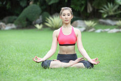 Young girl doing yoga in lotus pose in the lawn Royalty Free Stock Photos