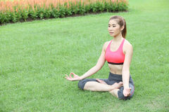 Young girl doing yoga in lotus pose in the lawn Royalty Free Stock Images