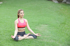 Young girl doing yoga in lotus pose in the lawn Stock Photos