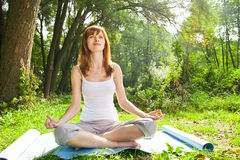 Young girl doing yoga lotus pose in park Stock Images