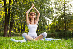 Young girl doing yoga (lotus pose) in the park Stock Images