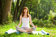 Young girl doing yoga (lotus pose) in the park Royalty Free Stock Photos
