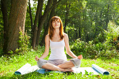 Young girl doing yoga (lotus pose) in the park Stock Photography