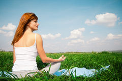 Young girl doing yoga (lotus pose) in the park Stock Photo
