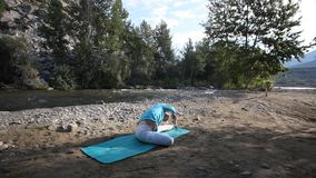 In nature, a young girl doing yoga stock video