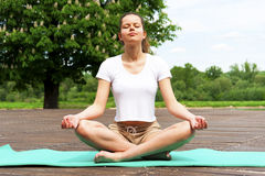 Young girl doing yoga in the park with closed eyes Stock Photo