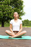 Young girl doing yoga in the park with closed eyes Royalty Free Stock Photography