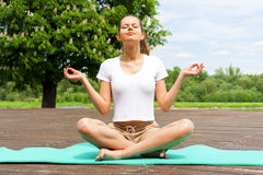 Young girl doing yoga in the park. Lotos position. Royalty Free Stock Images