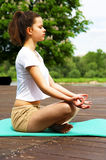 Young girl doing yoga in the park. lotos position. Stock Images
