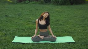 Young girl doing yoga in the park stock video