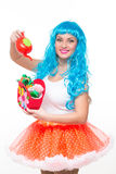 Young girl doll with blue hair. watering artificial flowers Royalty Free Stock Image
