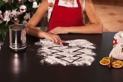 Young girl drawing christmas tree in the flour prepared to make Royalty Free Stock Photos