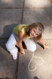 Young girl is drawing on the concrete ground Royalty Free Stock Photo