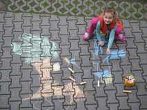 Young girl drawing. With crayons on the courtyard Stock Photography
