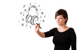 Young girl drawing headphone and musical notes Royalty Free Stock Photos