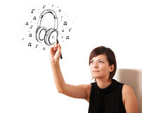 Young girl drawing headphone and musical notes Stock Photo