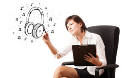 Young girl drawing headphone and musical notes Stock Image