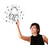 Young girl drawing headphone and musical notes Royalty Free Stock Image
