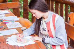 Young girl drawing mandala. Young woman drawing mandala pattern with a red pencil in the wooden garden house Royalty Free Stock Photography