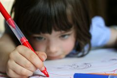 Young girl drawing with marker pen stock image