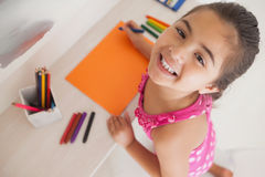 Young girl drawing on orange paper Royalty Free Stock Photography