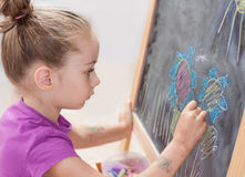 Young girl drawing a picture with a chalk on blackboard. Young blond five years old caucasian girl drawing a picture with a chalk on blackboard royalty free stock image