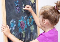Young girl drawing a picture with a chalk on blackboard. Young blond five years old caucasian girl drawing a picture with a chalk on blackboard stock photo