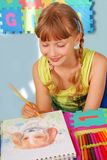 Young girl drawing a picture of dog. With colored pencils sitting in the room stock photos