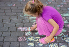Young girl drawing a picture outdoor with a chalk Stock Photography