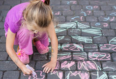 Young girl drawing a picture outdoor with a chalk Stock Photos