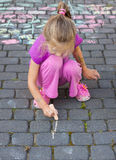 Young girl drawing a picture outdoor with a chalk Stock Images