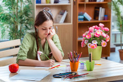 The young girl drawing pictures at home Stock Images