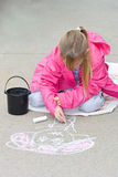 Young girl drawing with sidewalk chalk. Royalty Free Stock Photos