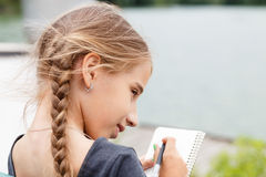 Young girl drawing sketch in notebook near pond Royalty Free Stock Photos