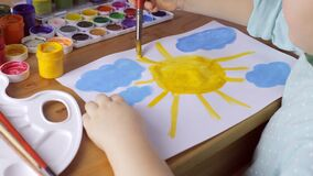 Young girl drawing yellow sun and blue clouds stock footage