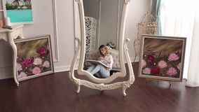 Young girl draws in the bedroom sitting on the floor, reflected in the mirror. A young talented girl draws at home in the bedroom sitting on the floor, it is stock footage