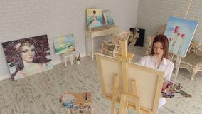 A young girl draws on canvas in the studio. A young girl in a white shirt draws on canvas in the studio for drawing among a variety of paintings. Art stock footage