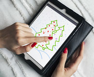 Young girl draws Christmas tree on the tablet Stock Images