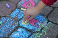 Young girl draws with the colourful chalks Stock Images