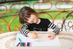 Young girl draws Halloween pumpkin outdoors Stock Photography