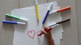 Young girl draws 3 hearts stock footage