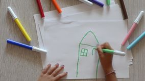 Young girl draws a house stock footage