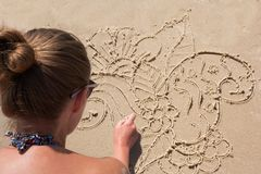 Young girl draws on the sand on the beach a zentangle, doodle. Young girl draws on the sand on the beach a zentangle, doodle stock image
