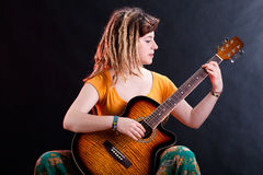 Young girl with dreadlocks playing guitar Stock Photos