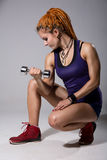 A young girl with dreadlocks training with dumbbells. Royalty Free Stock Photo
