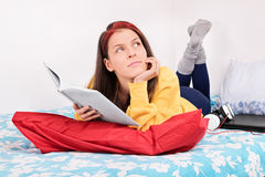 Young girl dream-reading on her bed Royalty Free Stock Images
