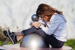 Young girl dreaming on a playground equipment Royalty Free Stock Images
