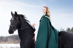 Young girl in dress with black horse in winter Stock Photo